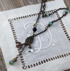 This Keyhole and Aqua Blue Glass Bead Necklace was handmade by me in my studio using aqua blue czech glass beads, antique brass chain, a single black glass bead. The center piece is a keyhole with dangling bird, crystal and aqua blue czech glass bead. This comes together and forms a Y
