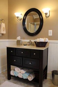 tan bathroom ideas, black sink vanity open at the bottom, black circle mirror.