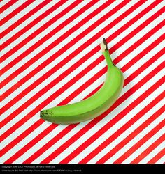 green banana on red-white background, colourful photo, colour blocking, food styling, still life photography