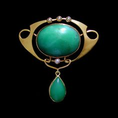 MURRLE BENNETT & Co. (1896-1914)  A large gold brooch set with a central cabochon chrysoprase and four pearls   within a whiplash mount. A chrysoprase drop below. Anglo/German c.1900.   Marks for MB & Co. and 15 ct. Size: Height 4 cm. Width 3.7 cm. (Fitted Case)  Lit.: Art Nouveau Jewelry. Vivienne Becker. Liberty Style. Academy Editions.