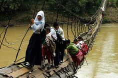 Kids climbing across a collapsed bridge to get to school... The ruler of Indonesia is the richest man in the world but the children have to risk their lives just to go to school!