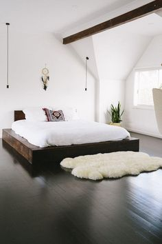 Gorgeous open floor plan bedroom with dark mahogany hardwood floors, a low profile platform bed with bright white bedding, a large sheepskin area rug, a pair of simple bronze bulb string pendant lights, dreamcatcher, and angled ceiling architecture. Love this minimalist and modern bohemian interior design!