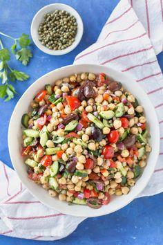 Mediterranean inspired chickpea salad with olives, cucumber, tomatoes, onion, in a white bowl on a blue background sitting on top of a small bowl of capers, a parsley sprig and a white and red striped kitchen towel.