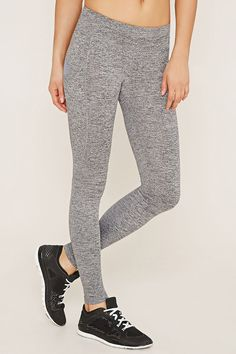 A pair of athletic leggings crafted from heathered knit with a side pocket, a hidden key pocket, and moisture management.