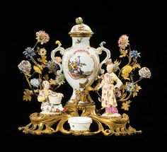 A LOUIS XV ORMOLU, MEISSEN, ST. ClOUD AND VINCENNES PORCELAIN CENTERPIECE Circa 1750 In the form of a table fountain, with central two-handled covered vase decorated with rocaille cartouche reserves of tropical birds on a white ground and further decorated with insects, the pierced handles above a foliate-cast spout with later foliate stop, flanked by Chinoiserie figures of a fishmonger and his wife, on acanthus-scrolled rusticated platforms issuing flowering trees with Vincennes porcelain…