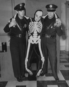 """1952 Two Los Angeles policeman and a skeleton named """"Mr. Statistic"""" attempt to warn drivers about traffic fatalities during Labor Day weekend."""