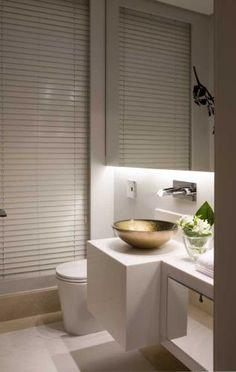 O lavabo de 2,50 m² de Marcelo Rosset tem cuba de vidro colorido de Murano, que fica suspensa sobre um tampo de mármore branco Sivec. A iluminação é embutida no painel onde está preso o espelho. Um painel de madeira é suporte para a persiana da Luxaflex, que esconde uma janela pequena