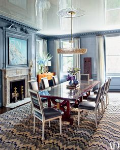 A midcentury Lobmeyr chandelier is suspended above the dining room's S. R. Gambrel–designed chairs and églomisé-top table; the painting, at left, is by Ed Ruscha, and the rug is by Beauvais.
