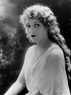 "Mary Pickford. Silent Film Actress. ""She founded United Artists and practically invented acting for the silver screen."" Pale powder and a strong lip because of black and white imagery on tv."
