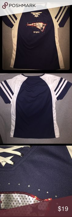 🏈 DRAFT SALE NFL New England Patriots Women's Top For sale is a size XL, NFL New England Patriots Women's V-neck Short sleeve Top. This item is produced by Majestic Fan Fashion and is comprised of 100% polyester. The front of the top features the New England Patriots logo which is comprised of red sequins, and silver rhinestones. See picture for close up detail. The v-neck features a lace up design with white string. Item is in excellent condition and ready to be shipped to the next…