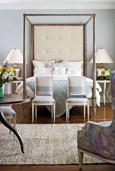 Artisan Poster Bed from Hickory Chair - in Traditional Home's 2011 Hamptons Showhouse. The extra-tall tufted off-white headboard is flanked by twin tables with identical lamps, and it's end-noted with a pair of matching white-painted side chairs. The monochromatic palette of icy blue is augmented by pale neutrals—oatmeals and off-whites.   Interior design: Ron Fiore   Serene Bedrooms   Traditional Home