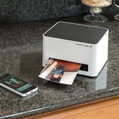 "This compact photo printer creates its own Wi-Fi network to connect with all iPhones, iPads, Samsung Galaxies and all other Android devices. Take it to parties for instant photo fun — it makes beautiful photos in three sizes: 4""x6"", 4""x11.2"" and 4""x16.4"". Print photos from any digital camera via PictBridge or USB cable. Uses mess-free cartridges that contain the paper and ink. Includes trial cartridge that makes 10 4""x6"" prints. Prints photos directly from digital cameras via ..."