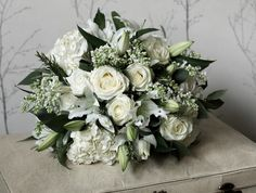 white wedding bouquet of lilies, lilacs, roses, hydrangeas white roses and eucalyptus and rosemary foliage