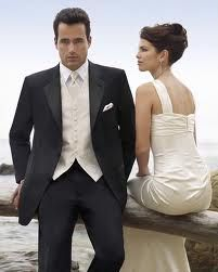 grooms men in a black suit, white shirt champagne or ivory vest and tie