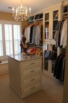 Wouldn't you love to hang out in this master closet?  With marble top center island, chandelier, window seat and glass front cabinets, this dressing area is as luxurious as it is practical.