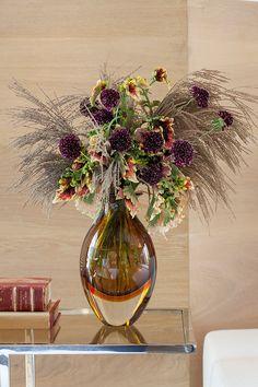 Decoração com mesa lateral com vaso de vidro com flores e livros.