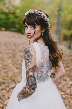 cool bride with red lipstick, heavy bangs, and tattoos on arm and back
