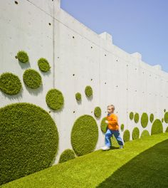 "Green wall idea with fake grass shapes  Rocamora Arquitectura. Nursery School ""La Monsina""ROCAMORA ARQUITECTURA, ALEXANDRE MARCOS OLIVARES"