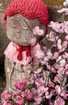 A statue of Jizo with flower offerings in the garden for unborn children, Zojoji Temple,Tokyo. Jizo Bosatsu (Bodhisattva), a beloved diety of Mahayana Buddhism, is the guardian of children, women, and travelers.  Grieving parents place toys and other offerings beside the statues to invoke protection of their child who has passed away.  #cemetery