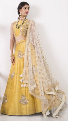 Yellow crop top with rosette embroidery in raw silk, a yellow lehenga with rosette embroidery in raw silk and a beige dupatta in tulle