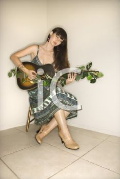 Royalty Free Photo of a Woman Sitting Playing Guitar
