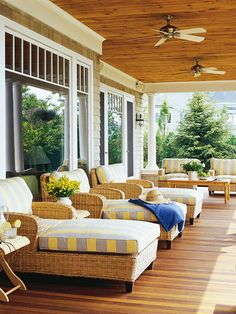 The airy feel and comfortable furniture welcome visitors to this beachy porch. It doesn't matter if your porch view is just the house across the street--turn it into a restful retreat. Make your porch feel like a day at the beach with wicker furniture; plush cushions covered in blues, whites, and yellows; and outdoor ceiling fans