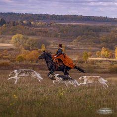 Woman riding side-saddle with 3 Borzoi