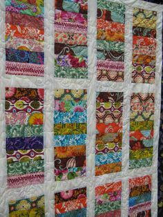 Baby Quilt - The center is made up of strips of fabric and white Kona cotton sashing. Wide border in a purple Kitty Yoshida fabric, City Girl. Floral and leaf quilting. Size: 37 x 55