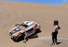 Marc Wams of team HRX waits for driver Erik Van Loon to get out of the car after crashing during in stage 6 from Arica to Calama during the 2013 Dakar Rally on January 2013 in Arica, Chile. Chile, Four Hundred, Rally Raid, Road Racing, Getting Out, South America, Boat, January 10, Stage