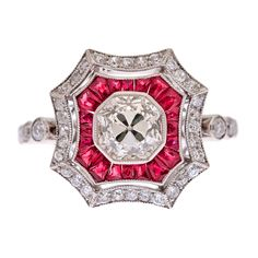 "Diamond & Ruby Platinum Art Deco Style Ring    Estate  Superbly hand crafted art deco style ring with a 1.01 carat old European cut diamond center stone. The diamond grades as H-I color, Vvs clarity and is very bright. The diamond is set in a mille grain edged platinum bezel, which almost appears to be an extension of the diamond. A scalloped border of custom cut red rubies makes the center diamond ""pop"", followed by a frame of brilliant diamonds the shape of which mirrors the rubies."