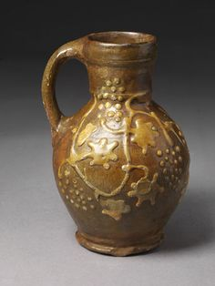 Jug of red earthenware with designs in white slip under a greenish-brown glaze. Reddish-brown sandy body. Pear-shaped with cylindrical neck and loop handle. Slip decoration of vine leaves and grapes. No lip on spout. Grooved strap handle. Triple thumbed at bottom. Ridged base, slightly concave.  Place of Origin  Buckinghamshire, England (probably, made) England, Great Britain (made) Date  ca. 1600 to 1650 (made)