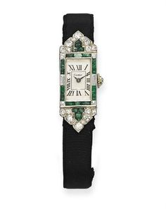 A LADY'S ART DECO EMERALD AND DIAMOND TANK WRISTWATCH, BY CARTIER   The rectangular cream dial with Roman numerals and blued steel hands within a buff-top emerald and diamond frame, shield-shaped shoulders and deployant buckle, to the black silk strap, mechanical movement, circa 1925, 15.2 cm inner circumference, with French assay marks for platinum and gold  Dial signed Cartier, nos. 17506, 25503, 2304  Movement signed European Watch and Clock Co. Inc, no. 25503