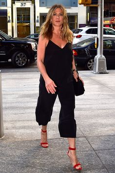 19 June Jennifer Aniston paired her black cropped jumpsuit with a pair of cherry-red sandals while out in New York. - HarpersBAZAAR.co.uk