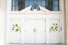 Floral wreaths by Stems of Dallas elegantly adorn this simple entrance! Photo by Jess Barfield Photography. #wedding #wreaths #white