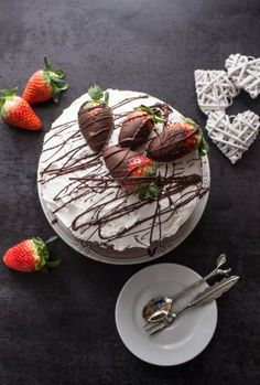 A delicious Vanilla Yogurt Cake filled with whipped cream and strawberries, topped with chocolate dipped strawberries and chocolate drizzle.
