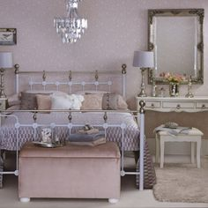 Feng shui bedroom mirror in room with wrought-iron double bed, dressing table, stool and chandelier