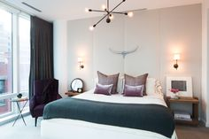 White bedroom with purple pillows and throw, antlers