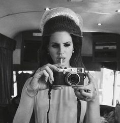 Lana Del Rey taking a Polaroid in the mirror