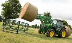 5M Series Tractor with baler and loader lifting hay bale
