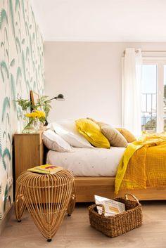 Dormitorio con cama de madera y papel pintado de hojas, con ropa de cama amarilla_427822