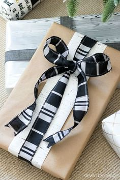 Leftover wrapping paper scraps and wire-edged black and white ribbon from Homegoods dress up a plain kraft paper present! (sponsored pin)