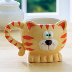 "Give your favorite cat lover a gift that will be appreciated every day. Ceramic mug is 4"" tall, with a cat's-tail handle! Details: - Dishwasher/microwave safe. - Holds 12 ounces. - Specify orange tabb"