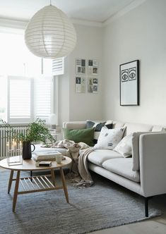Soft pale beige living room with natural details, green accents and a minimalist sofa from British Design Shop