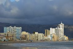 """Strand """"beach walkers"""" during winter - Hibernian Towers and other Golden Mile apartment blocks together with the Hottentots-Holland mountain range as backdrop. Sup Surf, Water Photography, Windsurfing, Big Challenge, Coastal Homes, Mountain Range, Towers, San Francisco Skyline, Surfboard"""