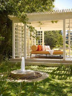 Backyard pergola landscaping idea with fountain added beauty.