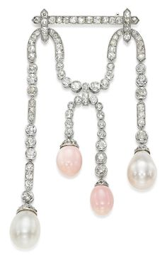 A BELLE EPOQUE NATURAL PEARL, CONCH PEARL AND DIAMOND BROOCH, JOSEPH CHAUMET, CIRCA 1910. Set with four natural pearl and conch pearl drop pendants later adapted, each with diamond cap, suspended from a pavé-set diamond twin-scroll, with French assay marks for platinum, with indistinct jeweller's mark for J. Chaumet. #Chaumet #BelleÉpoque #brooch