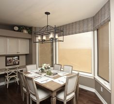 Mock roman shades in vertical stripe and screen shades behind.
