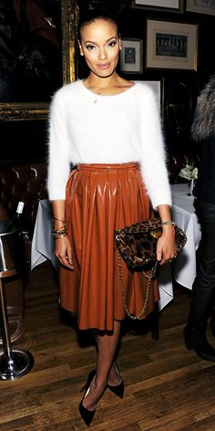 Selita Ebanks mixed textiles, stepping out in a fuzzy white sweater that she paired with a high-shine patent dark camel midi skirt. A delicate necklace, a pile of gold bangles, a leopard-print purse and black Christian Louboutin pumps completed her look.