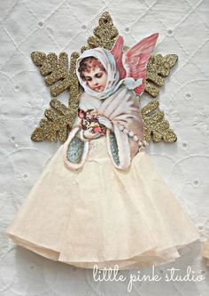 You could totally DIY that - print out a vintage image from The Graphic Fairy, add tissue paper or a coffee filter as the skirt, get a cheapo gold star from the Dollar Tree. GENIUS.