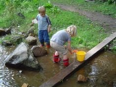 Nature playground De Speeldernis in Rotterdam Searching for small water creatures, the smallest snails, in a creek.